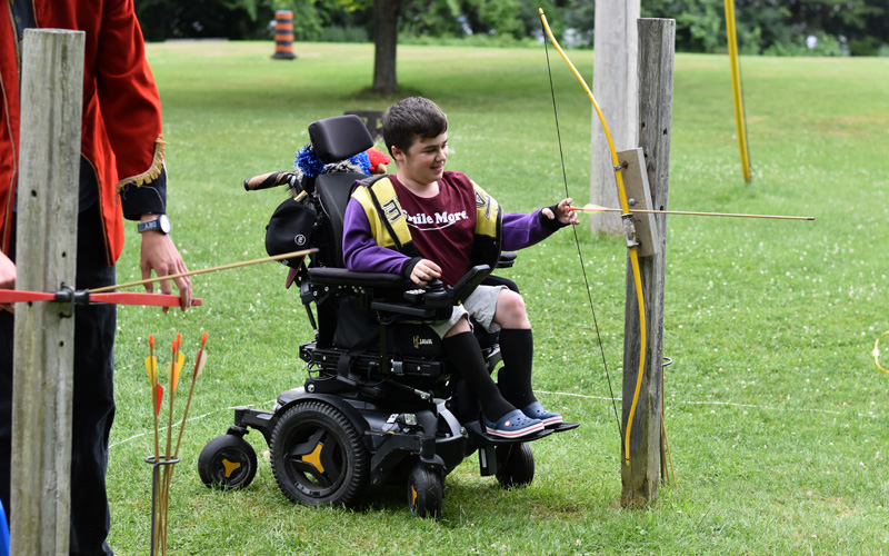 A boy performs archeery from a wheelchair
