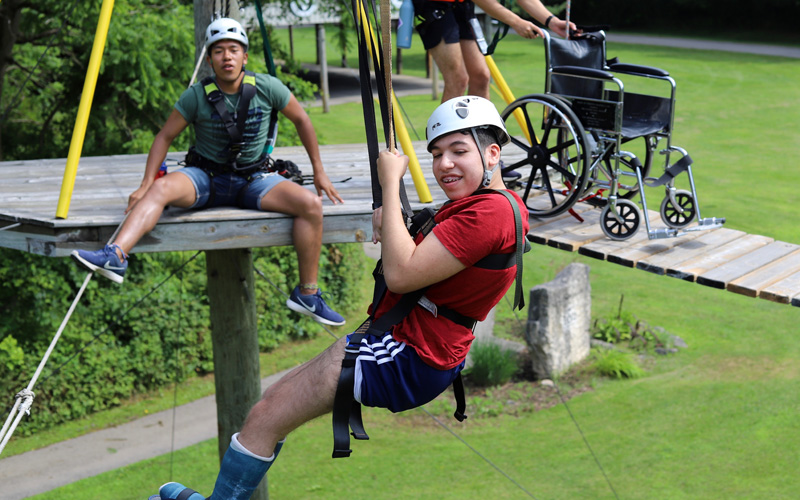 A young man zip lines on the high ropes course with his wheelchair left behind on the platform
