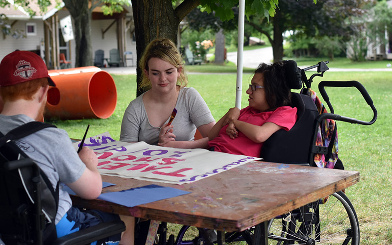 Kids do arts and crafts outside at an Easter Seals Camp
